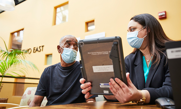doctor holding tablet looking at patient