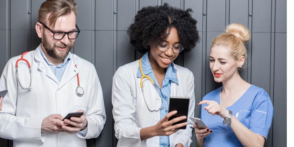 three doctors looking at their phones
