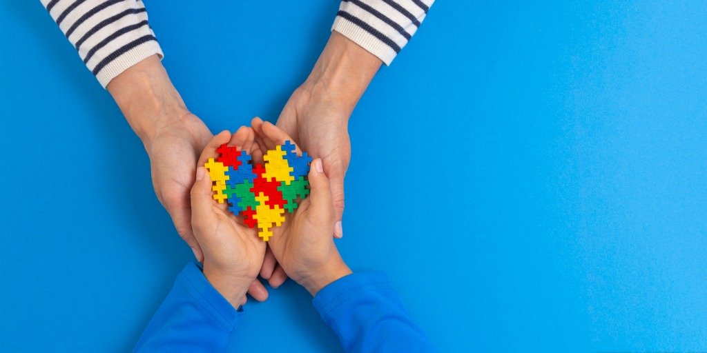 hands holding puzzle pieces for Autism awareness